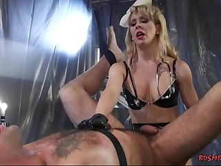 Busty light-haired dominatrix playing with her slave boy