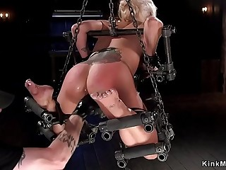 Waxed blonde in device bondage toyed